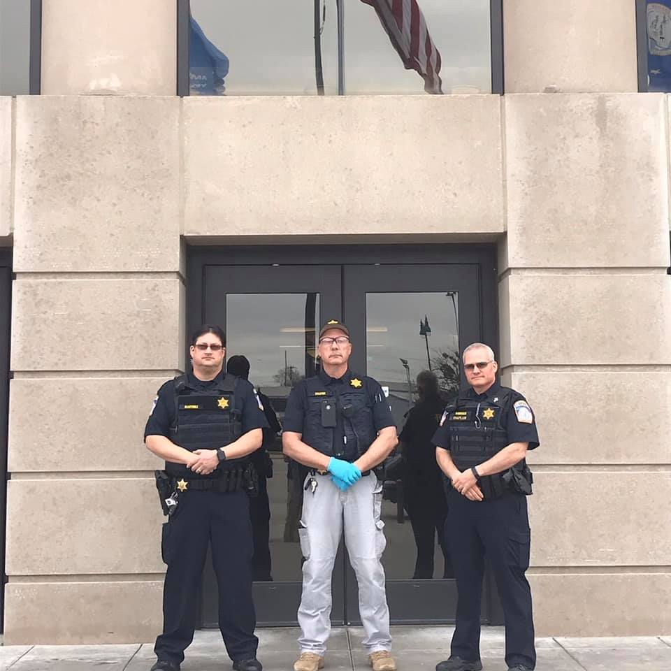 3 officers in front of the court